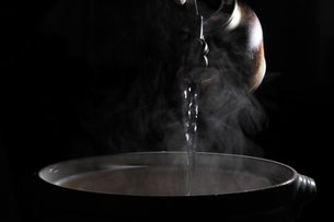 沸騰したお湯をなべに注ぐの写真素材 [FYI00498250]