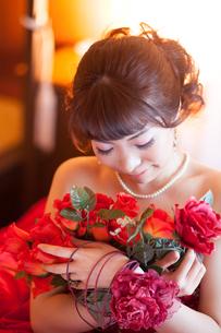 赤いドレスを着た女性と赤い花の写真素材 [FYI00498508]