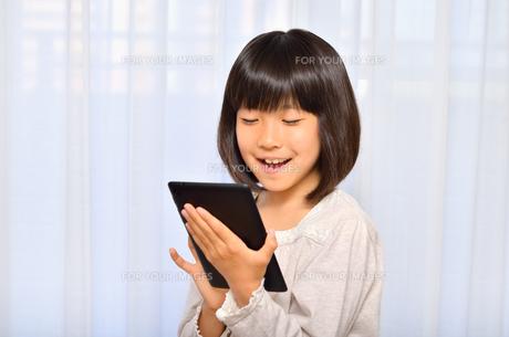 タブレット端末を操作する女の子の写真素材 [FYI00541517]