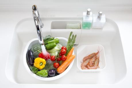 システムキッチンでの野菜の水洗いの写真素材 [FYI00545615]