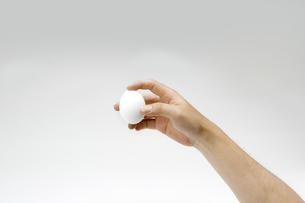 白い卵を持つ男性の手の写真素材 [FYI00551780]