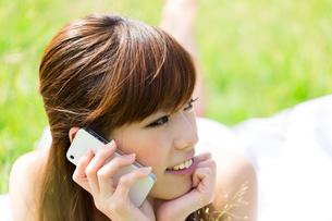 芝生の上で携帯電話を使う女性の写真素材 [FYI00556915]