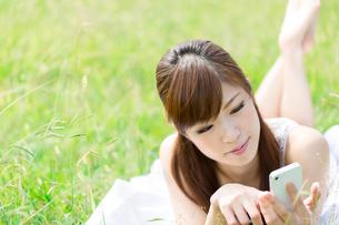 芝生の上で携帯電話を使う女性の写真素材 [FYI00556923]
