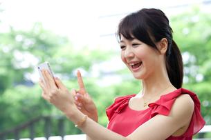 屋外で携帯電話を使う女性の写真素材 [FYI00557300]