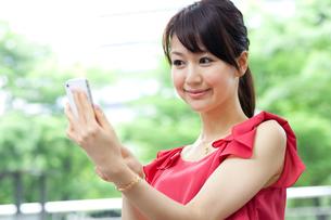 屋外で携帯電話を使う女性の写真素材 [FYI00557302]