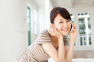 携帯電話を使う若い女性の写真素材 [FYI00557329]