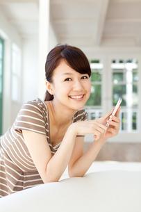 携帯電話を使う若い女性の写真素材 [FYI00557331]