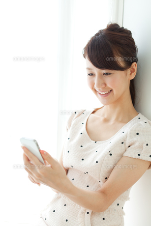 携帯電話を使う若い女性の写真素材 [FYI00557406]