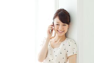 携帯電話を使う若い女性の写真素材 [FYI00557408]