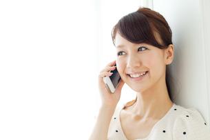 携帯電話を使う若い女性の写真素材 [FYI00557410]