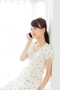 携帯電話を使う若い女性の写真素材 [FYI00557411]
