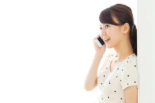 携帯電話を使う若い女性の写真素材 [FYI00557416]