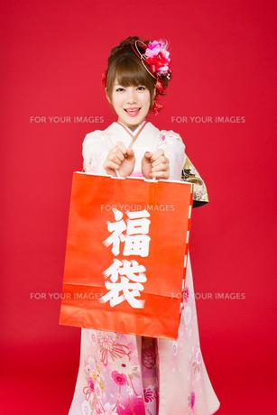 赤い背景で振袖を着た女性の写真素材 [FYI00557699]