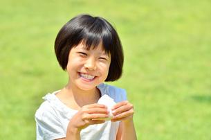 芝生広場でおにぎりを食べる女の子の写真素材 [FYI00602763]