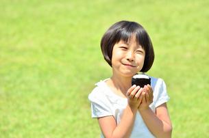芝生広場でおにぎりを食べる女の子の写真素材 [FYI00602764]