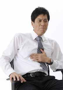 胃を押さえ顔をしかめるビジネスマンの写真素材 [FYI00603343]