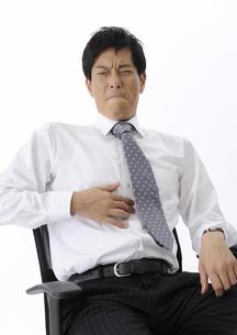 胃を押さえ顔をしかめるビジネスマンの写真素材 [FYI00603345]