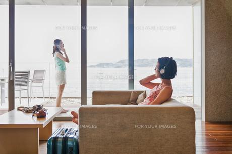 音楽を聴く女性と電話する女性の写真素材 [FYI00603422]