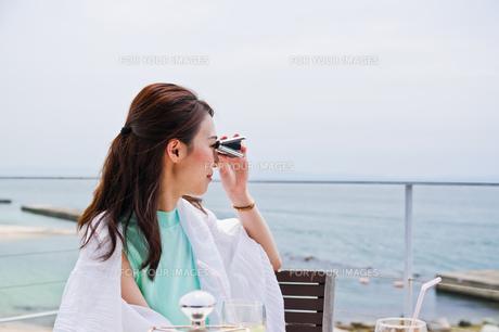 オペラグラスで遠くを見る女性の素材 [FYI00603430]