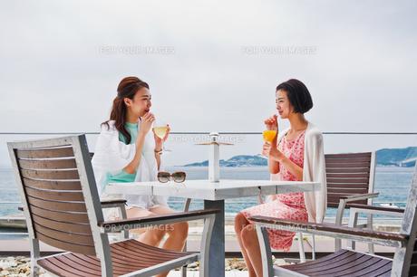 テラスで飲み物を飲む女性の素材 [FYI00603432]