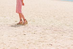 砂浜を歩く女性の足元の素材 [FYI00603470]