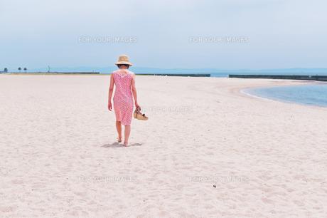 砂浜を歩く女性の後ろ姿の素材 [FYI00603474]
