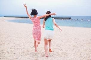 砂浜を走る二人の女性の写真素材 [FYI00603478]