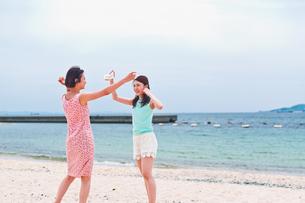 砂浜ではしゃぐ二人の女性の素材 [FYI00603480]