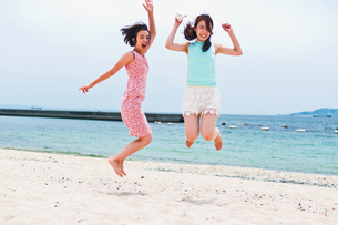 砂浜でジャンプする二人の女性の素材 [FYI00603482]