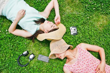芝生に寝転ぶ二人の女性の写真素材 [FYI00603495]