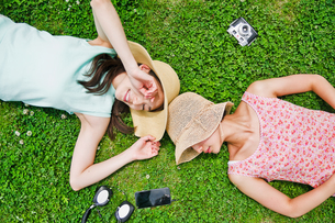 芝生に寝転ぶ二人の女性の素材 [FYI00603496]