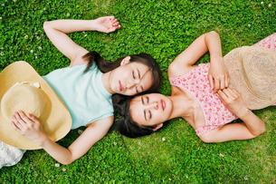 芝生に寝転ぶ二人の女性の素材 [FYI00603497]