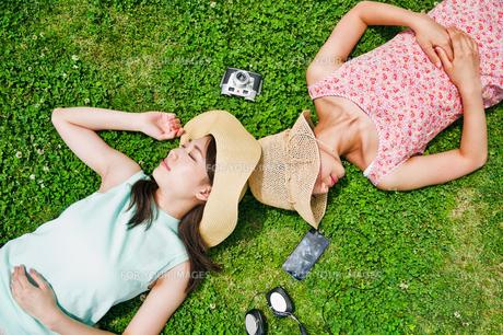 芝生に寝転ぶ二人の女性の素材 [FYI00603498]
