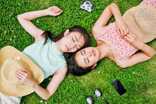 芝生に寝転ぶ二人の女性の写真素材 [FYI00603499]