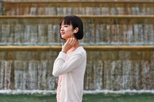 音楽を聴きながら歩く女性の素材 [FYI00603521]