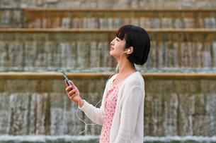 スマホで音楽を聴く女性の素材 [FYI00603522]
