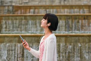 スマホで音楽を聴く女性の写真素材 [FYI00603525]