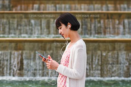 スマホで音楽を聴く女性の素材 [FYI00603526]