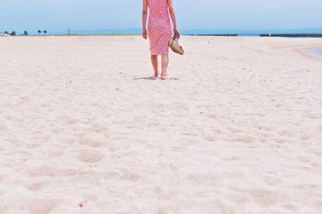 砂浜を歩く女性の後ろ姿の素材 [FYI00603574]