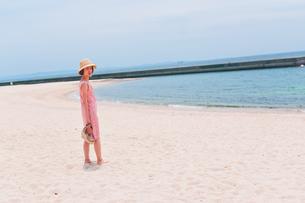 砂浜で振り向く女性の素材 [FYI00603577]