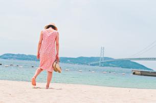 砂浜で歩く女性の後ろ姿の素材 [FYI00603579]