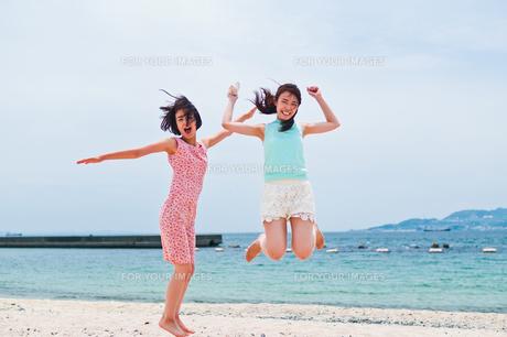 砂浜でジャンプする二人の女性の素材 [FYI00603585]