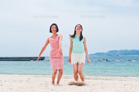 砂浜でジャンプする二人の女性の素材 [FYI00603588]