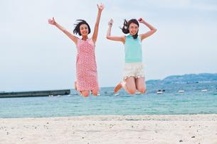 砂浜でジャンプする二人の女性の素材 [FYI00603589]