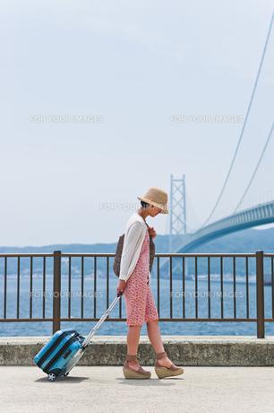 帽子を深く被ってキャリーケースを引く女性の素材 [FYI00603593]