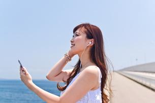 橋の上で音楽を聴く女性の素材 [FYI00603618]