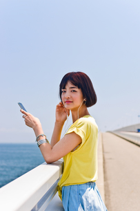 橋の上で音楽を聴く女性の素材 [FYI00603620]