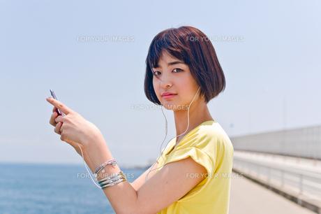 橋の上で音楽を聴く女性の素材 [FYI00603622]