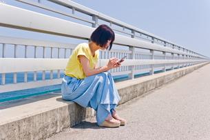 座ってスマホを操作する女性の素材 [FYI00603625]