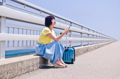 座ってスマホを操作する女性の写真素材 [FYI00603627]